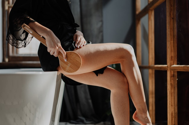 Frau behandelt Cellulite mit IR Massagegerät