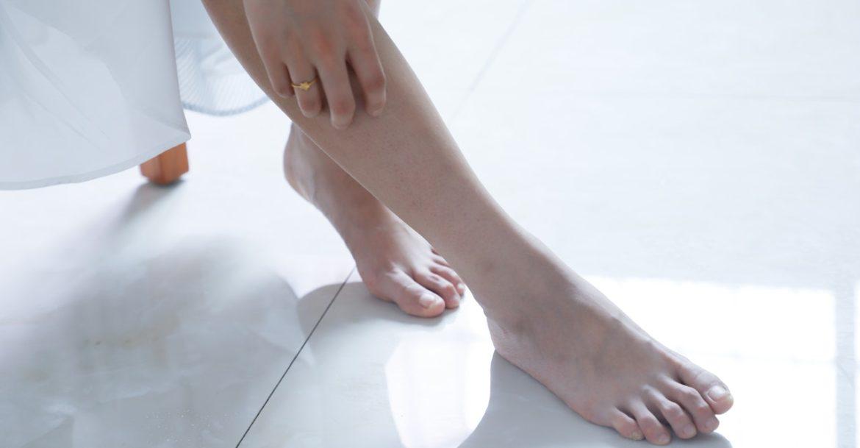 Weibliche Füße auf Fliesen mit einer Infrarot Fußbodenheizung