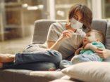 Mutter nimmt Fieber des Kindes
