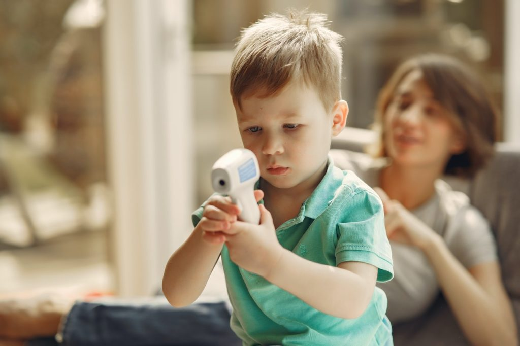 Kind schaut sich Infrarot Thermometer an