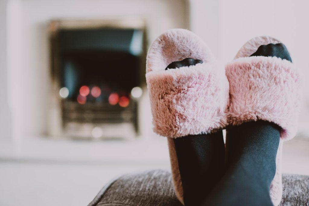 Person mit flauschigen Schuhen im warmen Raum