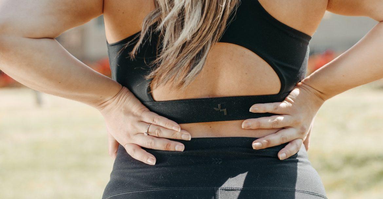 Frau fasst sich an den Rücken