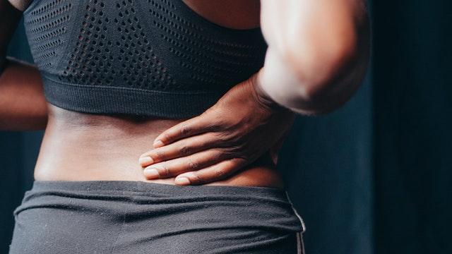 Junge Frau mit Muskelschmerzen
